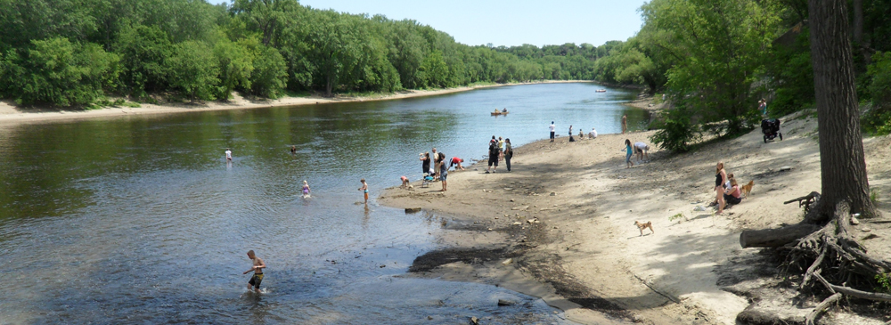 People playing on shore at the confluence of Minnehaha Creek and the Mississippi River