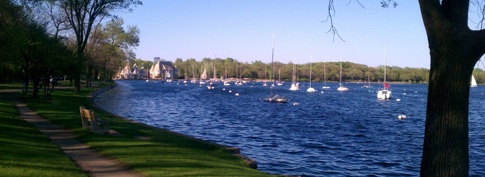 Photo of the Lake Harriet shoreline looking toward the bandshell with sailboats in the foreground, Minneapolis, Minnesota