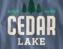 Detail of Cedar Lake design on indigo blue long-sleeve t-shirt
