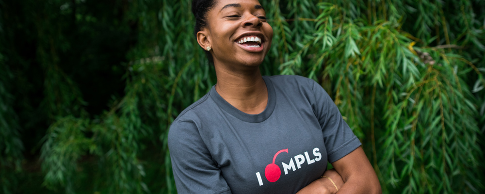 Young black woman wearing a charcoal grey I Cherry MPLS t-shirt in a park setting