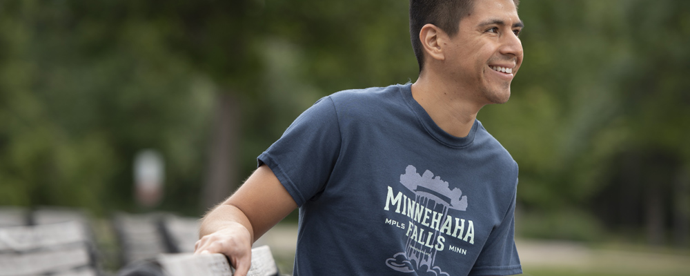 Young man wearing blue Minnehaha falls t-shirt on park bench