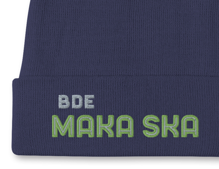 Close-up view of embroidered Bde Maka Ska design on navy blue winter beanie