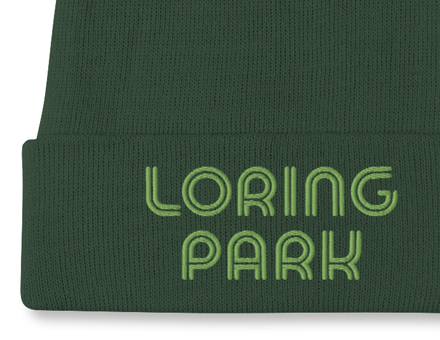 Close-up view of embroidered Loring Park design on dark green winter beanie