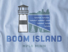 Close up view of Boom Island logo design on light blue long sleeve t-shirt