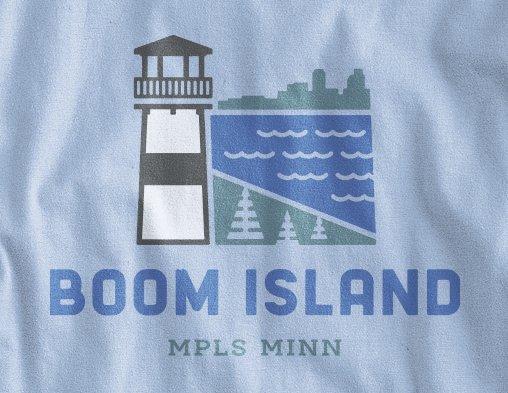 Close up view of Boom Island logo design on light blue long sleeve t-shirt