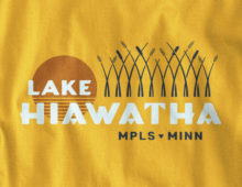 Close up view of Lake Hiawatha logo design on gold long sleeve t-shirt