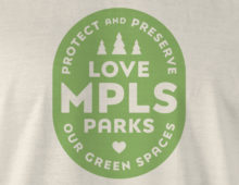 Detail of green Love MPLS Parks badge logo on soft cream t-shirt